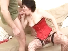 Granny in a red corset and stockings shows her tricks on a dick