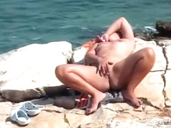I caught a nudist girl stimulating her sensitive clitoris on the beach