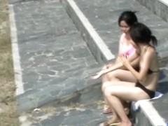 Asian babes relaxing on the beach get a boob sharking.