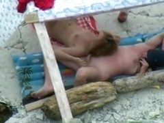 Voyeur tapes a nudist couple having oral sex at the beach