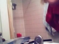 Voyeur captures a hot brunette naked in the bathroom
