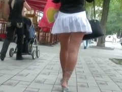 Voyeur video of a woman in high heels and white skirt