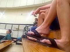 woman dangling flip flops in gym