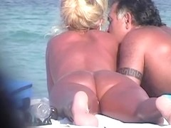 Hot beach handjob scene of tantalizing naked woman jerking husband.s penis
