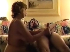 Wife gives her man a handjob, blowjob and titjob on the sofa.