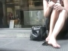 Upskirt spy cam shot of a sexy blonde sitting on a curb.